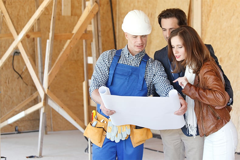 49538366 - foreman shows house design plans to a young couple